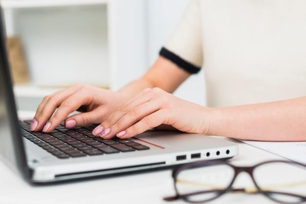 Mulher, em, luz, digitando, ligado, teclado laptop Foto gratuita