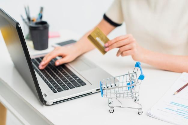 Mulher, em, luz, sentando, com, cartão crédito, em, tabela, com, laptop Foto gratuita