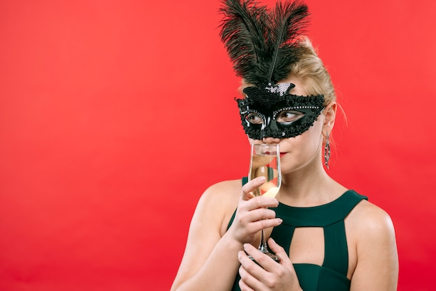 Mulher, em, máscara preta, com, vidro champanha Foto gratuita