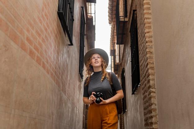 Mulher em meados de tiro com chapéu e câmera Foto gratuita