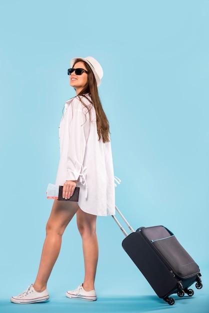 Mulher, em, óculos de sol, e, panamá, ficar, e, segurando, mala Foto gratuita