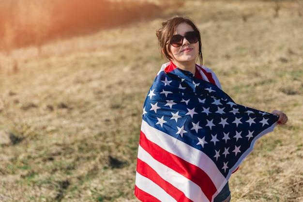 Mulher, em, óculos de sol, embrulhado, em, bandeira americana, olhando câmera Foto gratuita