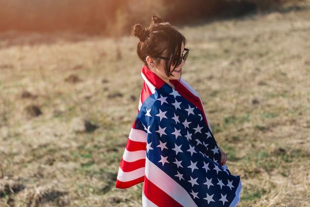 Mulher, em, óculos de sol, embrulhado, em, bandeira americana Foto gratuita