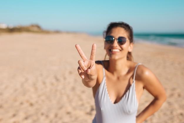 Mulher em óculos de sol fazendo v suspiro Foto gratuita