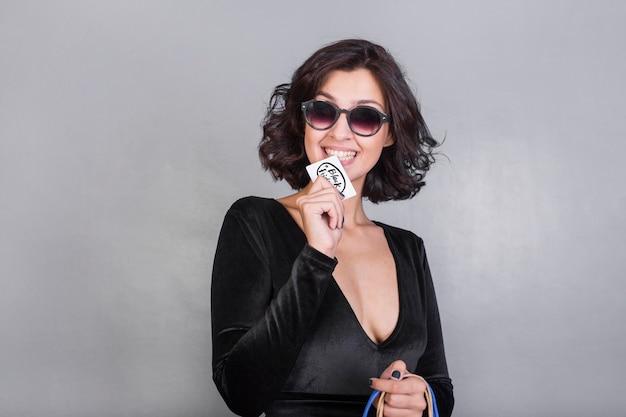 Mulher, em, óculos de sol, morder, cartão crédito Foto gratuita