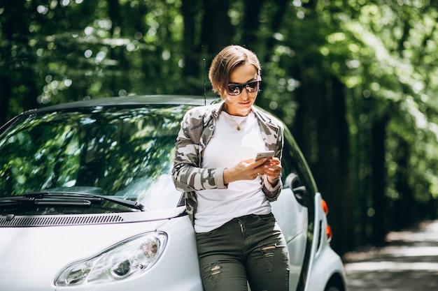 Mulher em pé ao lado do carro no parque usando o telefone Foto gratuita