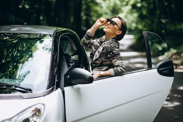 Mulher em pé ao lado do carro no parque Foto gratuita
