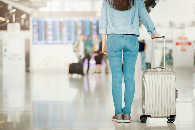 Mulher em pé em um aeroporto com bagagem Foto Premium