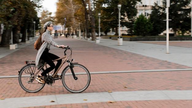 Mulher em pé na bicicleta - tiro longo Foto gratuita