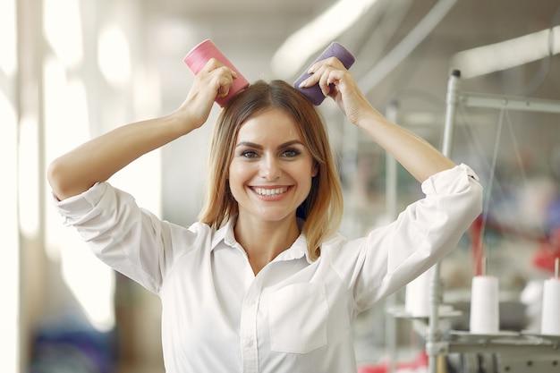 Mulher em pé na fábrica com um fio Foto gratuita