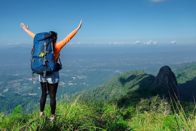 Mulher em pé no penhasco e empurre as mãos contra a montanha e a árvore Foto Premium