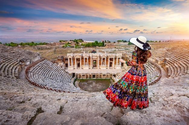 Mulher em pé no teatro da antiga cidade de hierápolis em pamukkale, turquia. Foto gratuita