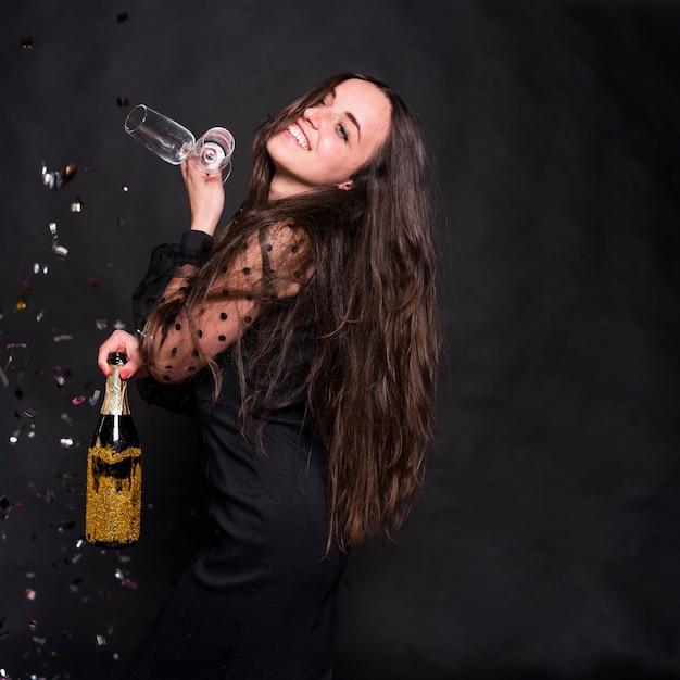 Mulher, em, pretas, com, garrafa champanha, e, óculos Foto gratuita