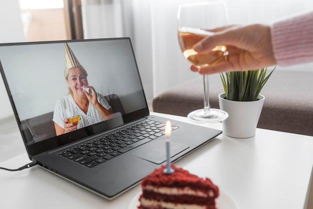 Mulher em quarentena comemorando aniversário com amigos no laptop e bolo Foto gratuita
