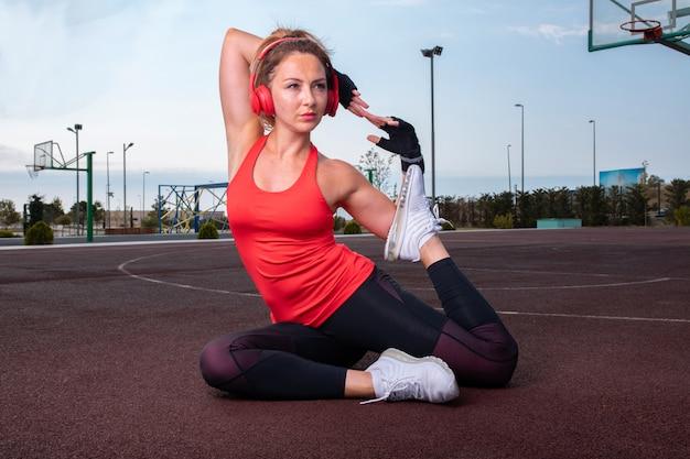 Mulher em roupas de esporte sagacidade fones de ouvido vermelhos, sentado no campo de basquete e fazendo treinamento de ginástica. Foto gratuita
