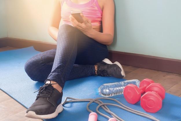 Mulher em roupas de fitness usando smartphone, estilo de vida saudável e conceito de treino Foto gratuita
