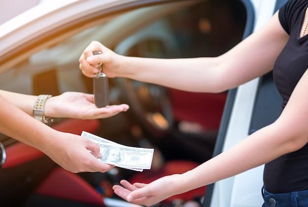 Mulher, em, showroom, dar, dólares, dinheiro, e, levando, teclas, de, car Foto Premium