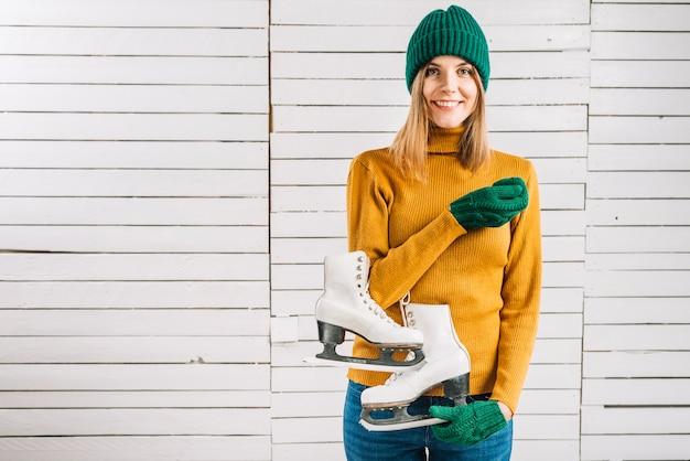Mulher, em, suéter amarelo, segurando, patins Foto gratuita