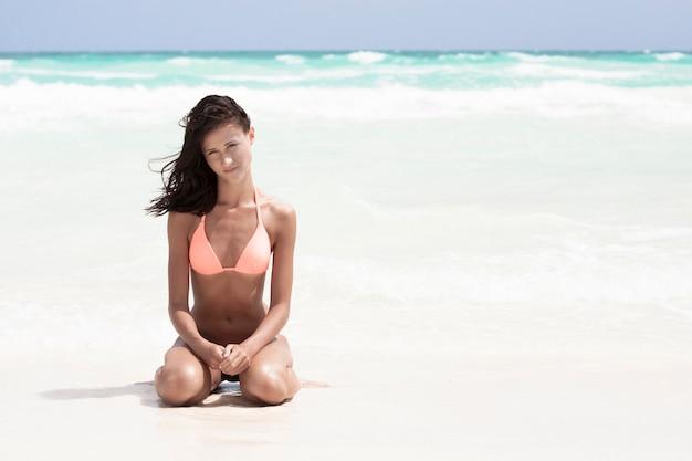 Mulher, em, swimsuit, sentando praia Foto gratuita
