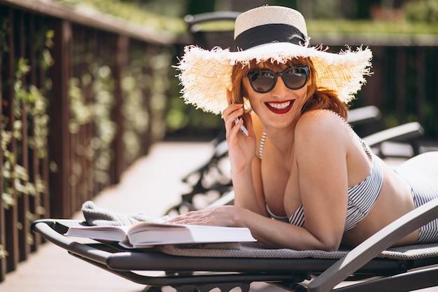 Mulher, em, terno natação, mentindo, ligado, um, cama, e, lendo um livro Foto gratuita