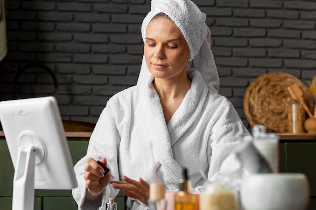 Mulher em tiro médio pintando as unhas Foto gratuita