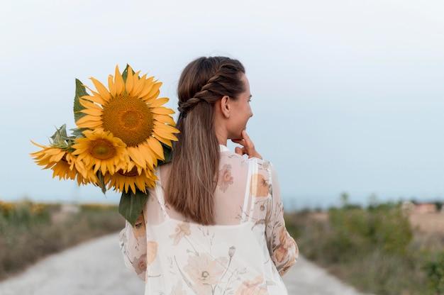Mulher em tiro médio segurando flores Foto gratuita