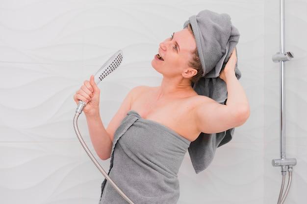 Mulher em toalhas cantando no chuveiro Foto Premium