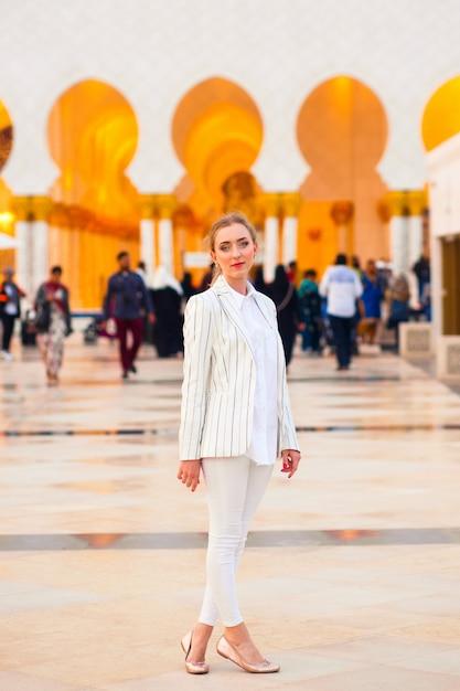 Mulher em trajes brancos antes da shez zayed grand mosque Foto Premium