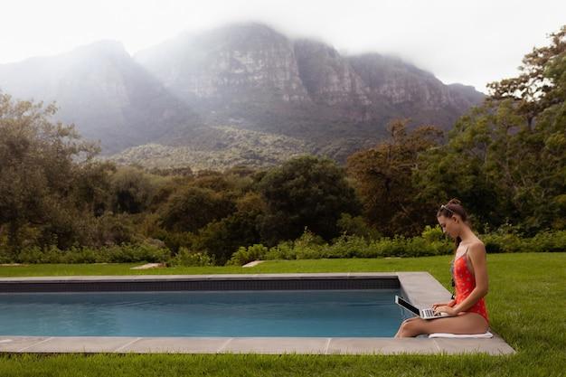 Mulher em trajes de banho usando laptop perto da piscina no quintal Foto gratuita