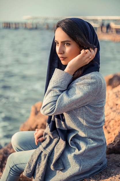 Mulher em trajes hijab à beira-mar Foto gratuita