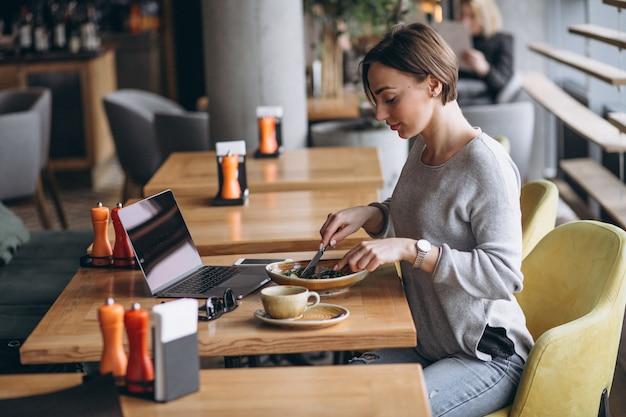 Mulher em um café almoçando e falando no telefone Foto gratuita