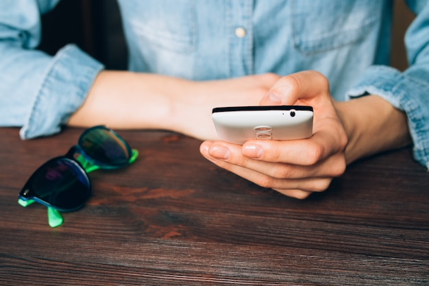 Mulher, em, um, camisa brim, segura, um, telefone móvel, e, sentando, em, um, tabela madeira, em, que, mentira, óculos de sol Foto Premium