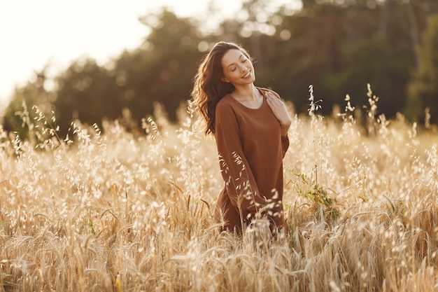Mulher em um campo de verão. morena com um suéter marrom. Foto gratuita