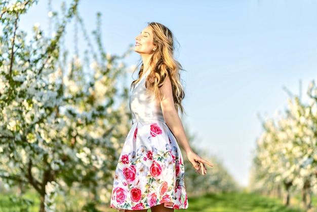 Mulher, em, um, florescendo, cereja, pomar, em, primavera Foto Premium