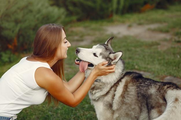 Mulher em um parque primavera brincando com cachorro fofo Foto gratuita