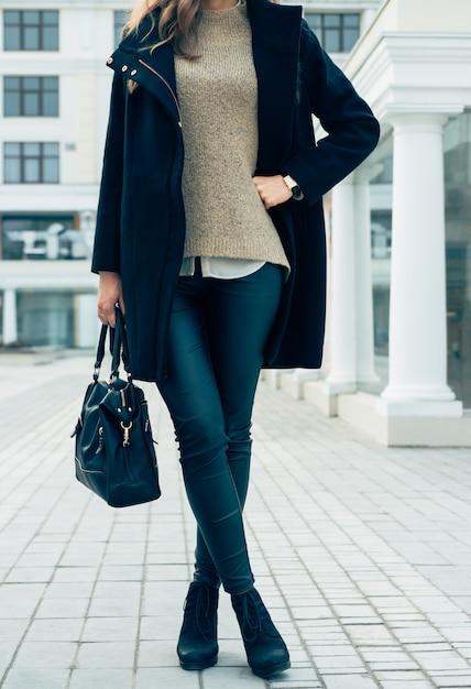 Mulher em um suéter, casaco preto e calças segurando uma bolsa enquanto caminhava na cidade Foto Premium