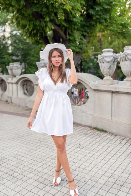 Mulher em um vestido branco e um chapéu branco Foto Premium