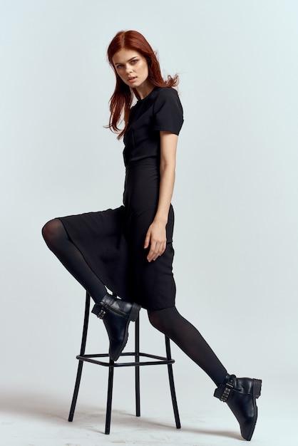 Mulher em um vestido preto, posando em um espaço claro, modelo Foto Premium