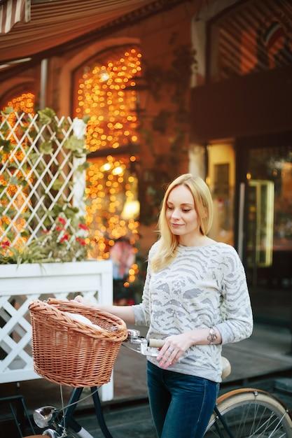 Mulher em uma bicicleta vintage na rua Foto Premium