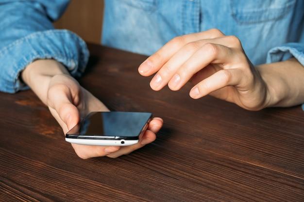 Mulher em uma camisa jeans segurando o celular e sentado em uma mesa de madeira Foto Premium