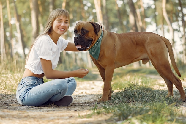 Mulher em uma floresta de verão brincando com cachorro Foto gratuita