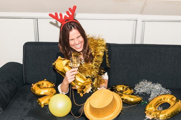 Mulher, em, veado, chifres, sentar sofá, com, champanhe Foto gratuita