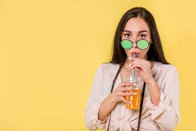 Mulher, em, verde, óculos de sol, com, suco Foto gratuita