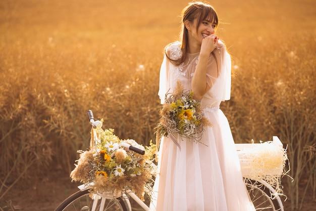 Mulher, em, vestido branco, com, bicicleta, em, campo Foto gratuita
