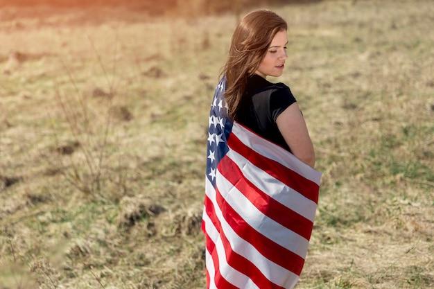 Mulher, embrulhado, em, bandeira americana, ligado, campo Foto gratuita