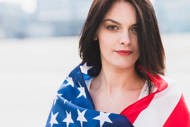 Mulher, embrulhado, em, bandeira americana, patrioticamente, olhando câmera Foto gratuita