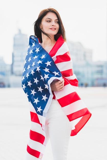 Mulher, embrulhado, em, bandeira americana, patrioticamente, olhar, ao longo, quadrado Foto gratuita