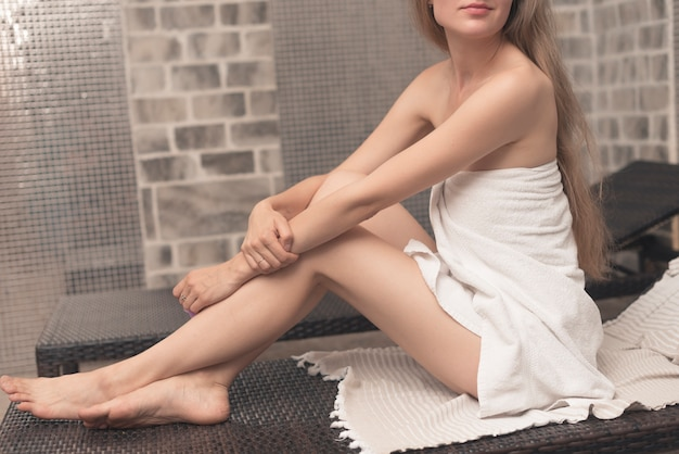 Mulher, embrulhado toalha, sentando, ligado, deckchair, em, spa Foto gratuita