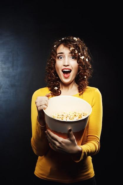 Mulher emocional assistindo filme de terror e parece assustado, sonhando alto Foto gratuita