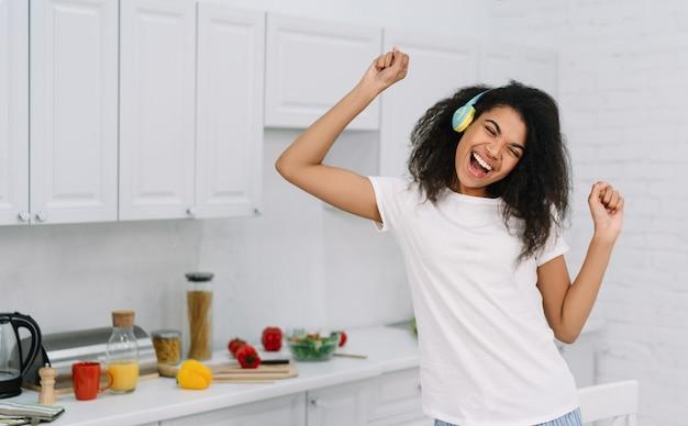 Mulher emocional feliz dançando em casa, se divertindo. retrato da música linda garota afro-americana usando fones de ouvido sem fio Foto Premium